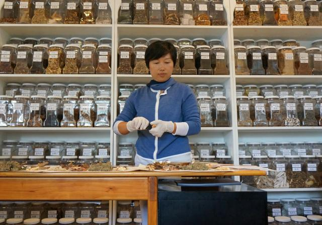 Ms Xiong preparing traditional chinese herbs