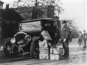 Policeman standing alongside wrecked car and cases of moonshine (Library of Congress, 1922)